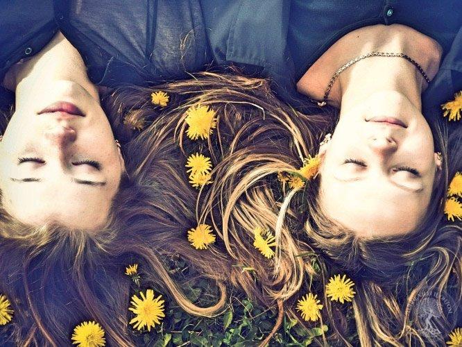 Naiset makaamassa voikukkien keskellä