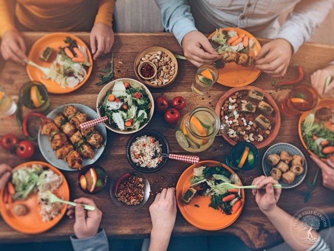 Villivihanneksista tehtyjä ruokia ja ihmisiä aterioimassa