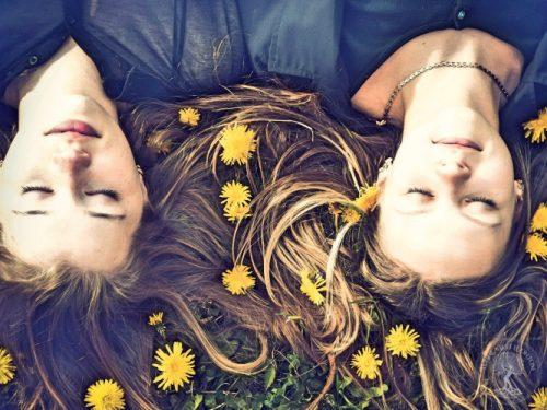 Women lying in the field with dandelions